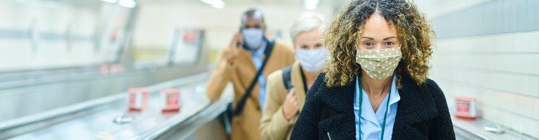 People walking in masks in the underground passage