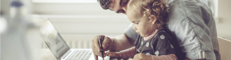 A father holding his baby on his lap and drawing something for him