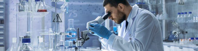 A microbiologist conducts research under the microscope.