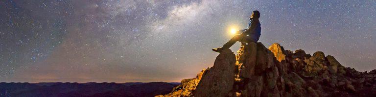 Man sitting on rocks admiring starry sky