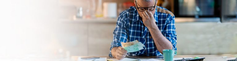 Man with sad expression seating at table and counting money