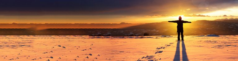 Person in snowy mountains with sunset background