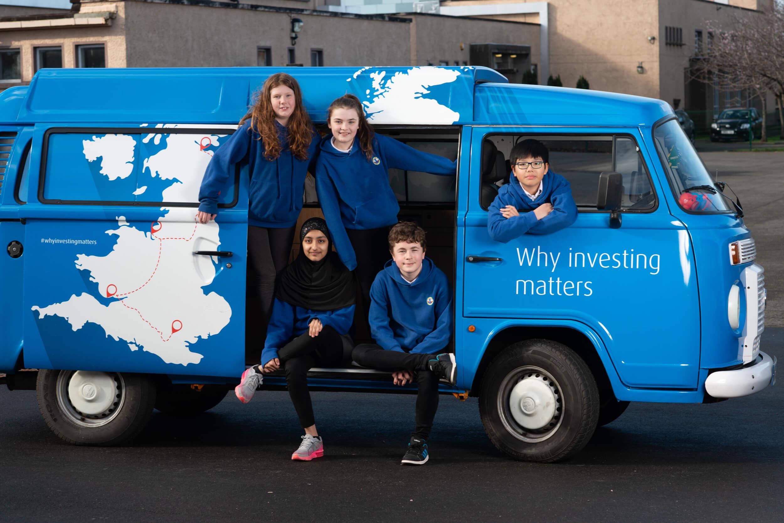 Five children sitting in the blue bus