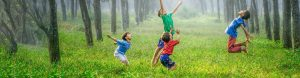 Children jumping in the forest