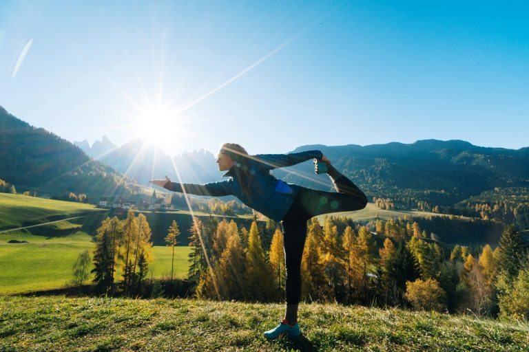 Women practices yoga in the sunny mountains