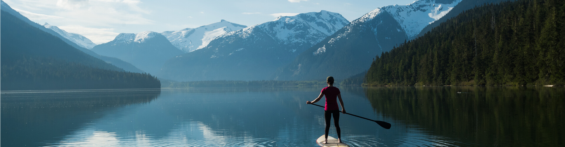 Woman standing on a paddleboard in the lake next to the mountains