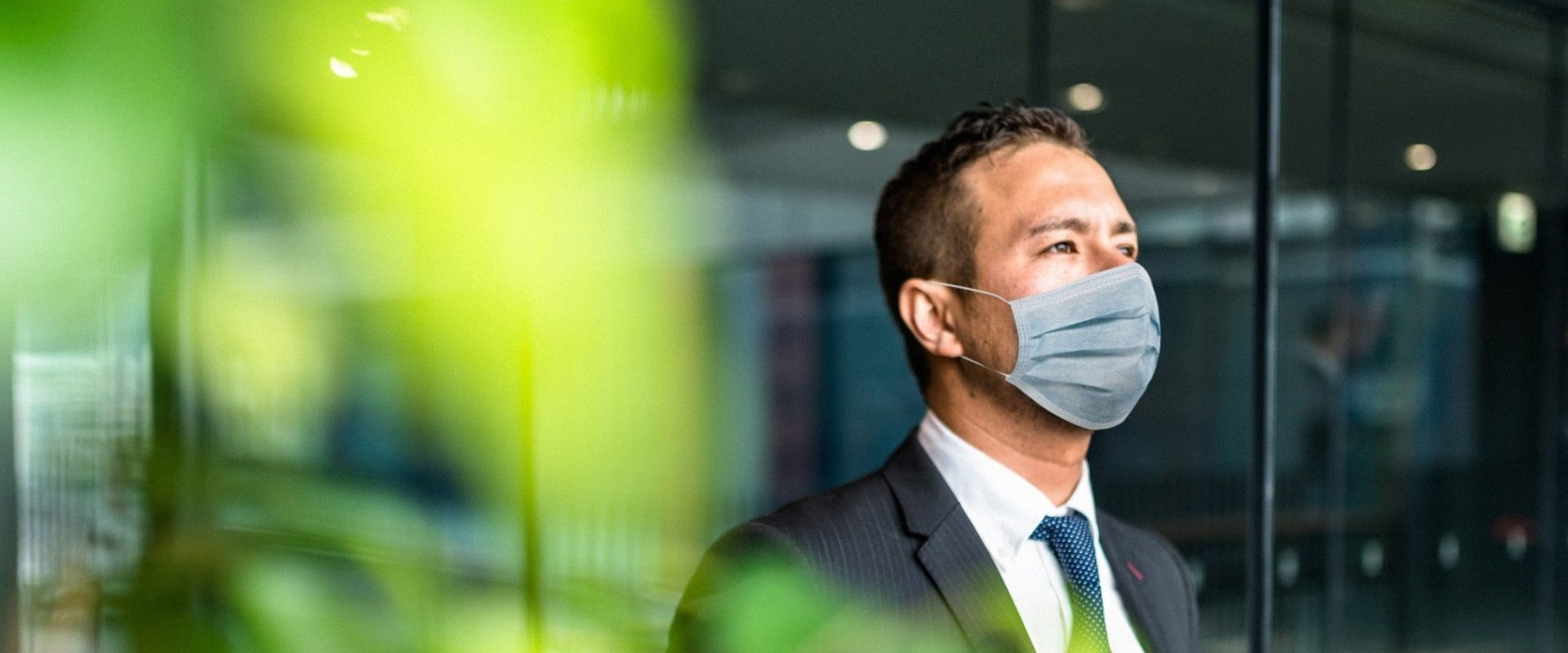 Man in medical mask standing by the window
