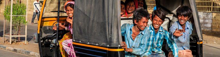 Laughing children riding a tuk tuk