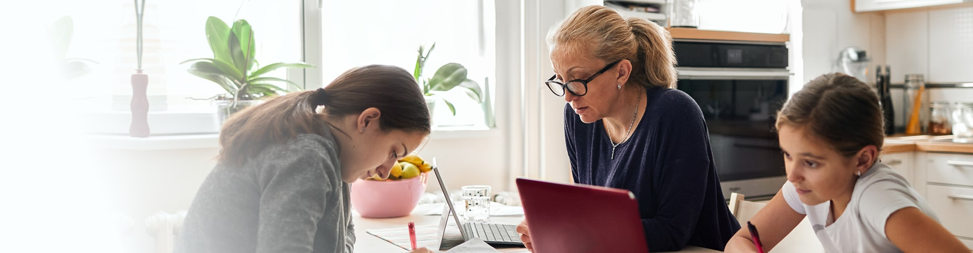Daughters doing their homework while mother working on the computer
