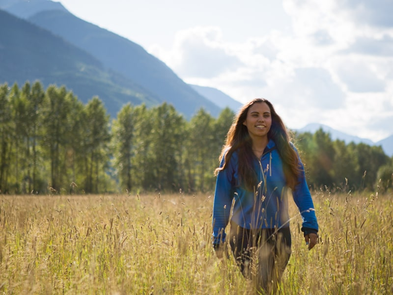 First Nations female walks through field smiling