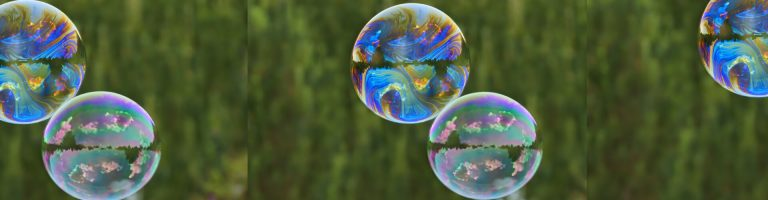 Bubbles floating in front of a green forest background
