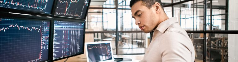 Investment analyst looking at data charts on different computer screens