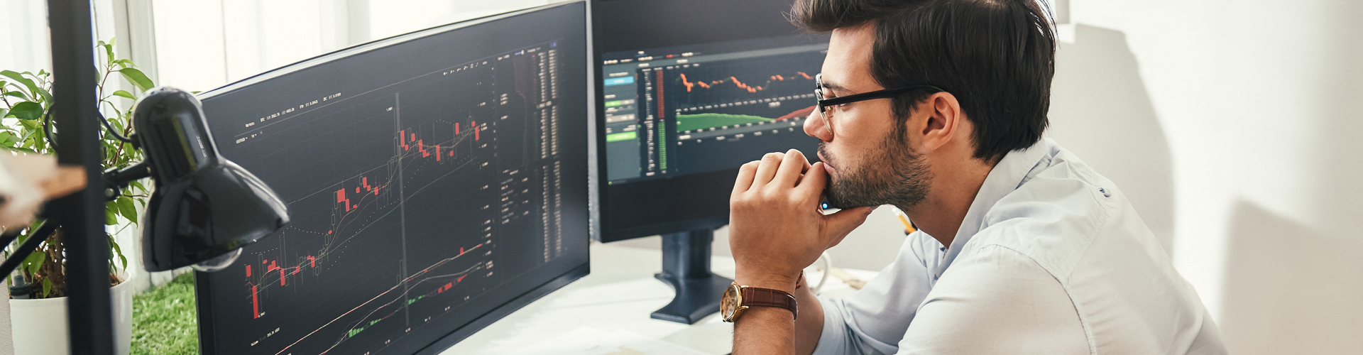Investment analyst looking at data chart on two computer screens