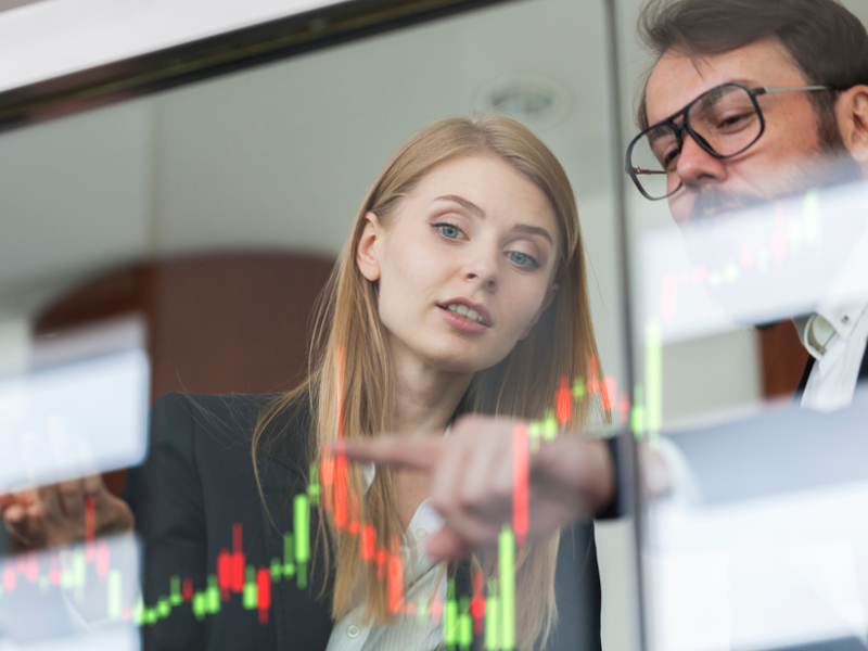 Investment analysts looking at data chart on computer screen