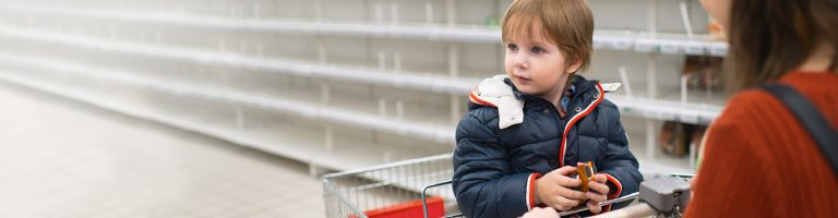 Boy sitting on a supermarket shopping trolley holing a car toy with his mother-