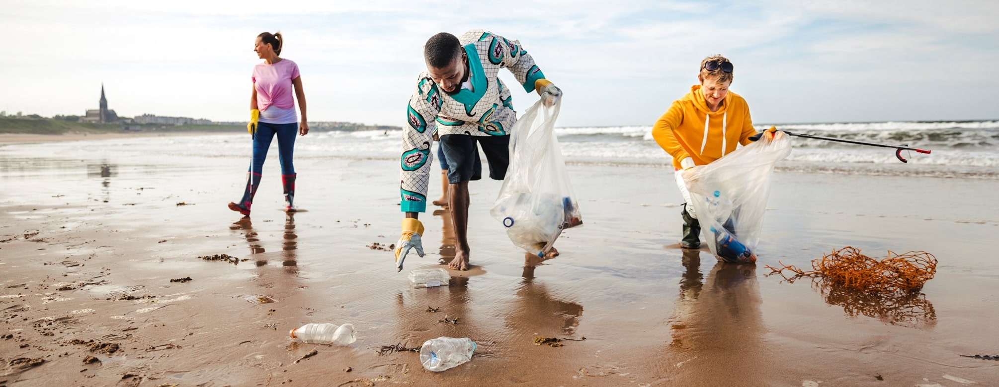 People collecting plastic waste on the beach.
