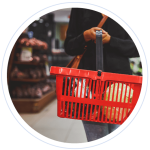 A woman holding a red shopping basket