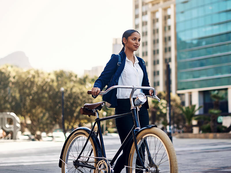 The woman is walking with the bicycle on the street