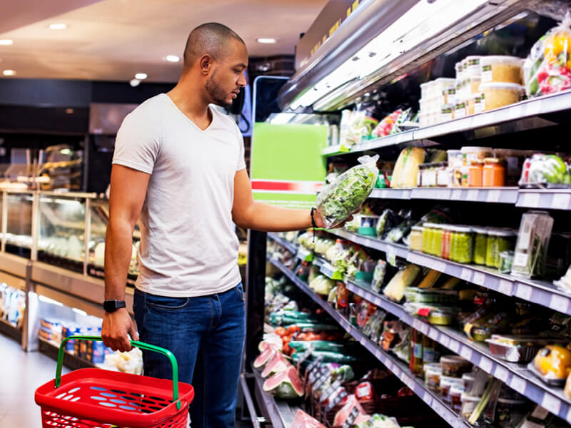 The man is shopping in the store and choosing lettuce