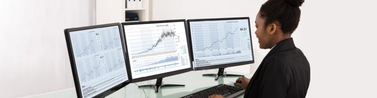 The woman analyzes the charts displayed on three monitors.