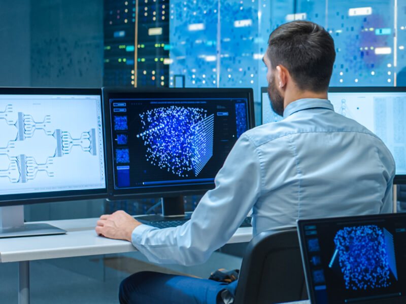 The man analyzes the data displayed on multiple monitors